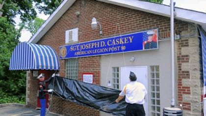 A new sign outside American Legion Post 80 in Ross is unveiled during the dedication ceremony of Sgt. Joseph D. Caskey American Legion Post 80, adopting the name of a local fallen marine.