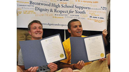 Brentwood's Sean O'Brien, left, and Monessen's Justice Rawlins, right, pose with proclamations presented to both schools by Brentwood's mayor to mark the schools' efforts Wednesday to combat the conflicts of this past winter.