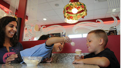 Brea Robinson watches as her son, Elijah, 2, grabs ice cream from his friend, Dominic Thomas, 6, Friday morning at the grand re-opening of the ice cream parlor at Sarris Candies in Canonsburg.