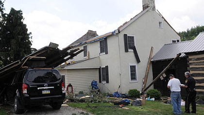Public safety officials from Westmoreland County survey damage to the home of Steve and Tracey Pelesky in Ligonier on Saturday after a suspected tornado hit the area Friday.