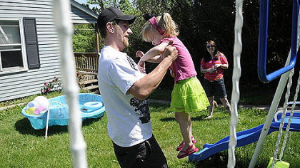 Jason Stiffler picks up his daughter, Holland Starr Stiffler, 2, while her mother, Rachel Bellaire, watches at their home Wednesday in North Fayette.