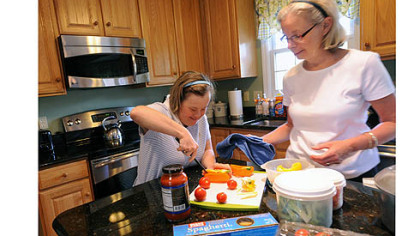 Marisa Murray, left, 38, and her mother, Nancy,  work together preparing veggies for their dinner salads in the kitchen of their home in Bethel Park.
