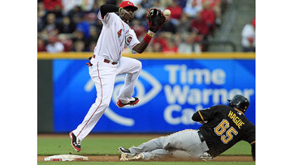 Pirates' Matt Hague steals second base as Reds second baseman Brandon Phillips catches a high throw in the third inning in Cincinnati.