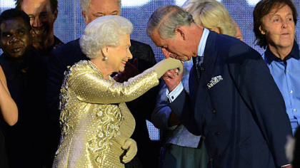 "Britain's Prince Charles kisses the hand of his mother, Queen Elizabeth, whom he called ""Mummy,"" on stage Monday as singer Sir Paul McCartney looks on at right after a concert outside Buckingham Palace in London, celebrating the queen's 60 years as monarch."