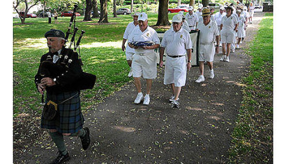 Dressed in their playing whites, members of the Frick Park Lawn Bowling Club parade behind bagpiper George Balderose to the dedication of the recently renovated club house May 28.