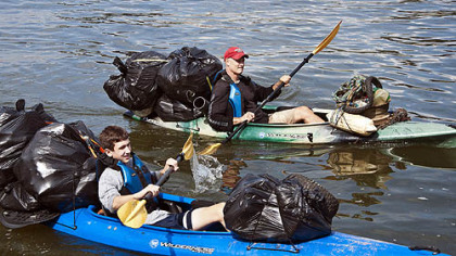 Evan Chernicky, left, and Steve Chernick paddle kayaks full of trash up the Allegheny River last September.