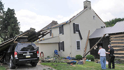 Public safety officials from Westmoreland County survey today the damage to the home of Steve and Tracey Pelesky in Ligonier, where a tornado hit Friday afternoon.