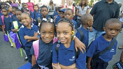 Second-graders Nicole Hurt, left, and Aliya Holmes enjoy their first day of school at William F. Harrity Elementary School in Philadelphia. Harrity is one of three failing schools that has been taken over by Mastery Charter Schools.
