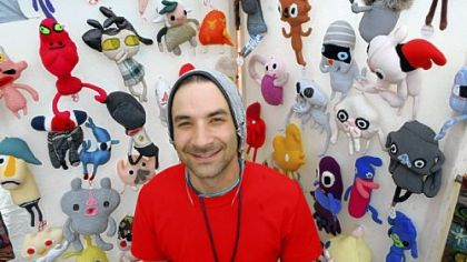 "Daniel Baxter stands with some of his ""Kreepy Dolls"" at his booth at the Three Rivers Arts Festival."