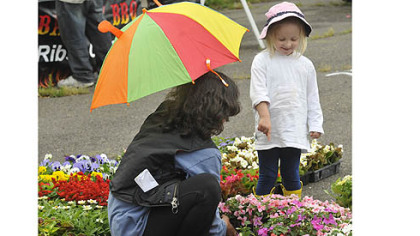 Swissvale's Camille Miller, 2, points to flowers that she likes with her nanny, Christine Capriotti, at opening day of the East Liberty Citiparks Farmers Market. Citiparks runs seven markets around Pittsburgh.