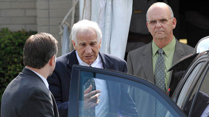 Jerry Sandusky leaves the Centre County Courthouse after the second day of testimony in his trial. At left is his attorney Karl Rominger; Centre County Sheriff, at right is Centre County Sheriff Denny Nau.