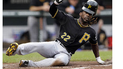 The Pirates' Andrew McCutchen loses his helmet as he slides into home plate for a run on a single by Matt Hague in the first inning.