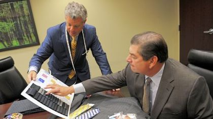 Robert Engel, left, of Tom James Co., shows samples to Emanuel DiNatale, chairman of accounting firm Alpern Rosenthal, at his office, Downtown.