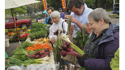 Shoppers at the Harvest Valley Farms stand at the East Liberty market.