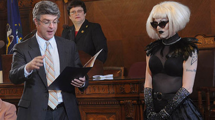 Councilman Patrick Dowd reads a proclamation he sponsored honoring drag queen Sharon Needles, right, during a city council meeting Tuesday. In the background is council President Darlene Harris.