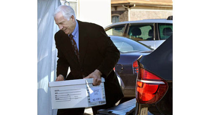 Jerry Sandusky helps unload case files from his attorney's car as he arrives at the Centre County Courthouse for the third day of his trial.