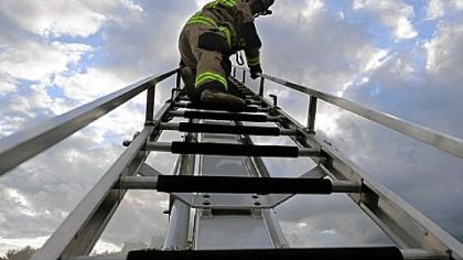 Lt. Don Knouse, a volunteer fire fighter from Moon, scrambles up the ladder of a &quot;squirt truck&quot; during a pump practice drill at the station in Moon.