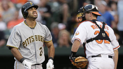 The Pirates' Pedro Alvarez, left, reacts after he struck out swinging to end the second inning. Orioles catcher Matt Wieters, right, looks on.