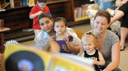 Awantika Kumar, left, of Carnegie, her 2-year-old daughter, Aarna, 15-month-old Elizabeth Glance and her nanny, Jennifer Matta, 28, attend a story-telling session at the Andrew Carnegie Library.