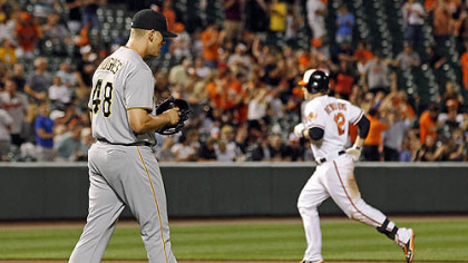 Pirates relief pitcher Jared Hughes, left, walks to the mound as Orioles' Mark Reynolds rounds the bases after hitting a solo home run in the eighth inning.