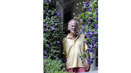 Basil Cox framed by clematis on his back porch.