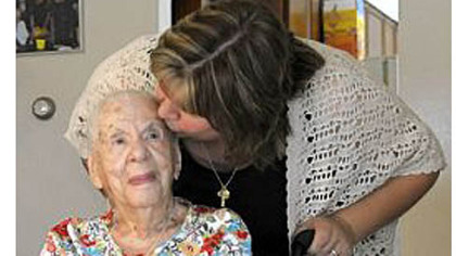 Frances Elliott, 100, gets a kiss from granddaughter Chrissy Corcoran at Mrs. Elliott's McKees Rocks home Friday.