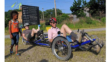 Felicia Williams, 6, of Hazelwood watches as Mary Shaw and her husband, Roy Weil, of Squirrel Hill pull away in their tandem recumbent tricycle to ride home Friday.