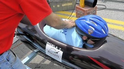 Macaila Ziolkowski, 12, of Pittsburgh is instructed to keep low in the cockpit by Steve Buzza, who recruited her for racing through a church group, before beginning her first race at the Greater Pittsburgh Soap Box Derby.