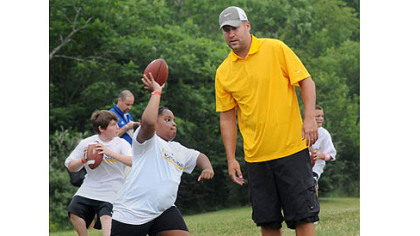 Steelers quarterback Ben Roethlisberger gives instruction in passing to youths during workouts at his football camp at Seneca Valley High School.