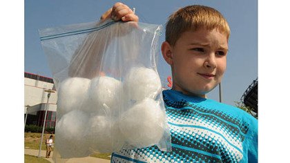 Cory Thurston, 8, carries the six snowballs he saved in the freezer from last winter.