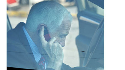 Jerry Sandusky talks on his phone inside the car as he arrives at the Centre County Courthouse for the seventh day of testimony in his trial Wednesday morning.