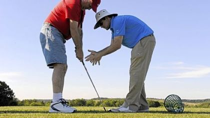 PGA teaching professional R.J. Wiegand helps Navy veteran Wilfred Tranter, 53, of Bethel Park with basic golf skills at Quicksilver Golf Club Wednesday evening. The program is through Robert Morris University.