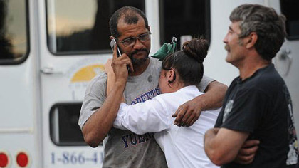 James Gatewood, left, hugging his daughter Jamie Gatewood, and Charles Kraus, all of Duquesne, stand outside Meade Brother's Trucking where a fatal shooting occurred in McKeesport today.