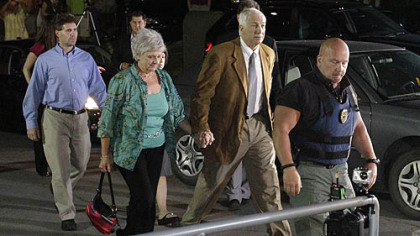 Former Penn State University assistant football coach Jerry Sandusky, right center, arrives with his wife Dottie, left center, at the Centre County Courthouse tonight to learn of the jury's decision.