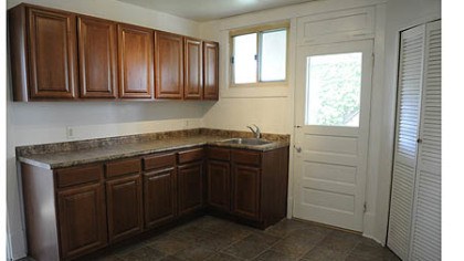 The second floor kitchen has a built-in pantry and offers hardwood cabinetry and laminate countertops with vinyl tile flooring.