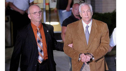 Jerry Sandusky is led in handcuffs by Centre County Sheriff Denny Nau after tonight's guilty verdict on 45 of 48 counts in Sandusky's sex abuse trial.