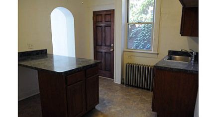 The first-floor kitchen has hardwood cabinets with a maple stain, laminate counter tops and vinyl-tile floor. Arched openings lead to a bathroom and the breakfast nook.