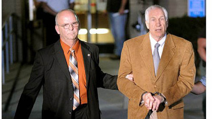 Jerry Sandusky is led in handcuffs by Centre County Sheriff Denny Nau after being found guilty Friday night on 45 counts of sexual abuse at the Centre County Courthouse in Bellefonte.
