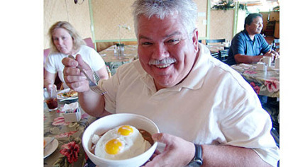 "Rick Sebak shows off a bowl of ""loco moco,"" featured in the new documentary ""Breakfast Special 2: Revenge of the Omelets."""
