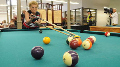 Phyllis Haduch of Mount Washington takes her shot while playing pool Monday with Francis Szewczyk after the reopening of the historic South Side Market House.