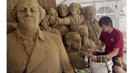 Martijn Rijerse, an artist with Sandsational, works on a sand sculpture of the signing of the Declaration of Independence, in Point State Park.