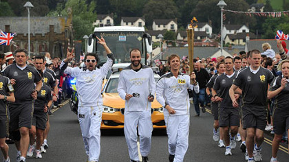 Torchbearers Matt Bellamy, Dominic Howard and Christopher Wolstenholme, from the band Muse, carry the Olympic Flame on the leg between Torquay and Teignmouth.