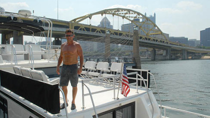 "Dave Wingrove, of Belle Vernon, stands on his boat ""Still Cruising"" on Friday morning outside of Heinz Field. Wingrove and many others have docked their boats on the North Shore in preparation for the Kenny Chesney concert weekend."