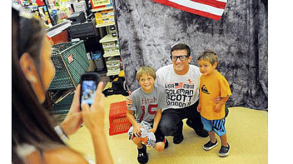Coleman Scott of Waynesburg poses with Ayden Pratt, 9, left, and Brody Pratt, 2, as their mother Kelli Pratt takes a photo Friday at a Giant Eagle in Rices Landing. Mr. Scott will be wrestling in the 2012 London Olympics next month.