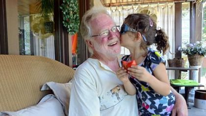 David Taiclet and his granddaughter Ava Hogan, 5, enjoy time together as she has her first garden tomato of the day.