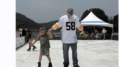 "Jared Bellan of Monaca and his son Jayden Bellan, 7, try out the ""Point SKATE Park"", an artificial ice rink set up at the 2012 EQT Pittsburgh Three Rivers Regatta at Point State Park."