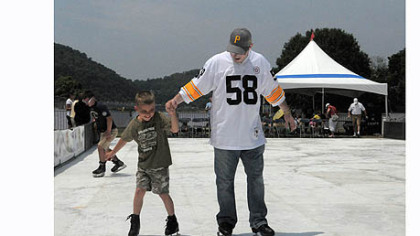 "Jared Bellan of Monaca and his son Jayden, 7, try out the ""Point SKATE Park"", an artificial ice rink set up at the 2012 EQT Pittsburgh Three Rivers Regatta at Point State Park on Saturday."