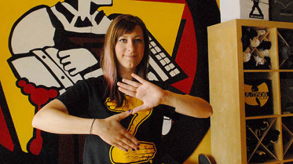 "Andrea Bible, who works at South Side T-shirt store CommonWealth Press, makes the Zoltan ""Z"" sign with her fingers while wearing the company's Zoltan shirt that is quickly becoming popular across the city."
