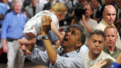 President Barack Obama lifts 9-month-old Nathan Maxwell Johnson of Youngstown into the air after speaking at a campaign event at Dobbins Elementary School in Poland, Ohio this morning.