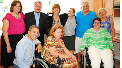 The Accessible Dreams development team with the Liadis family in their new accessible kitchen. In front, from left, are Duane Fauth, director of construction services, Accessible Dreams; Kathleen Kleinmann, CEO, TRIPIL; and Valerie Liadis. In the back row, from left, are Cindy Bodnar, director of housing services, Accessible Dreams; Richard Zatta, ADA consultant, Accessible Dreams; Lucy Rooth, executive director, Accessible Dreams; Bridget Coyne, attorney, Regional Housing Legal Services; and Thomas and Catherine Liadis.